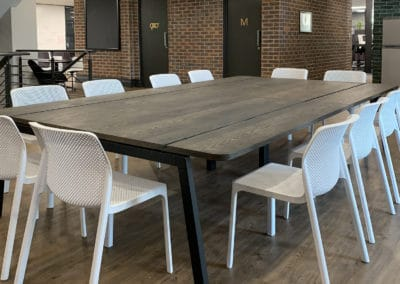large wooden table with white chairs